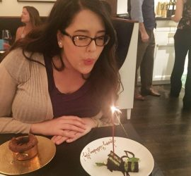 Photo of Aly Seidel blowing out candles at dinner at Pineapples and Pearls